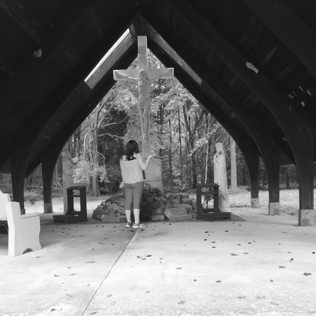 girl praying in front of cross and statue
