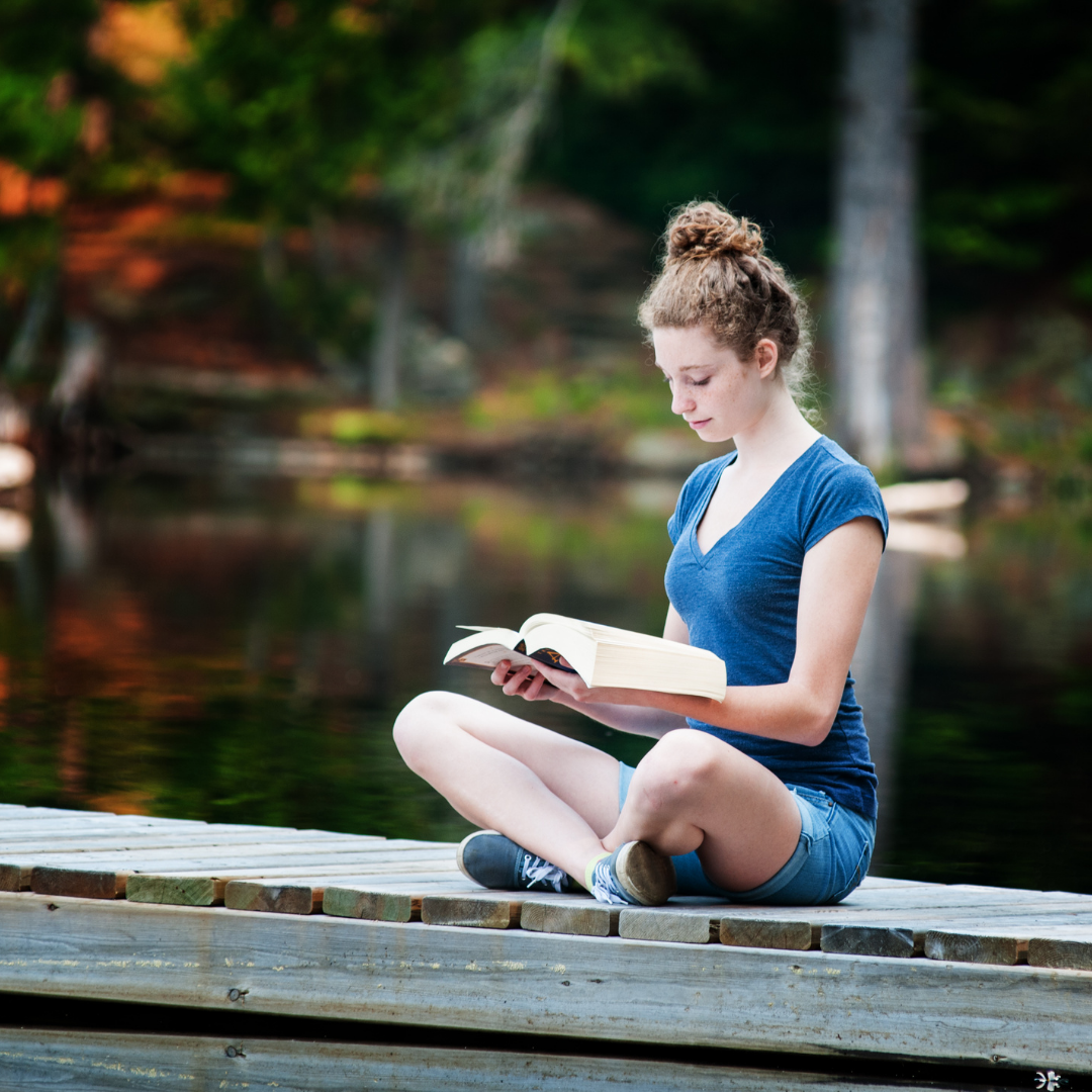 woman reading Bible on a dock