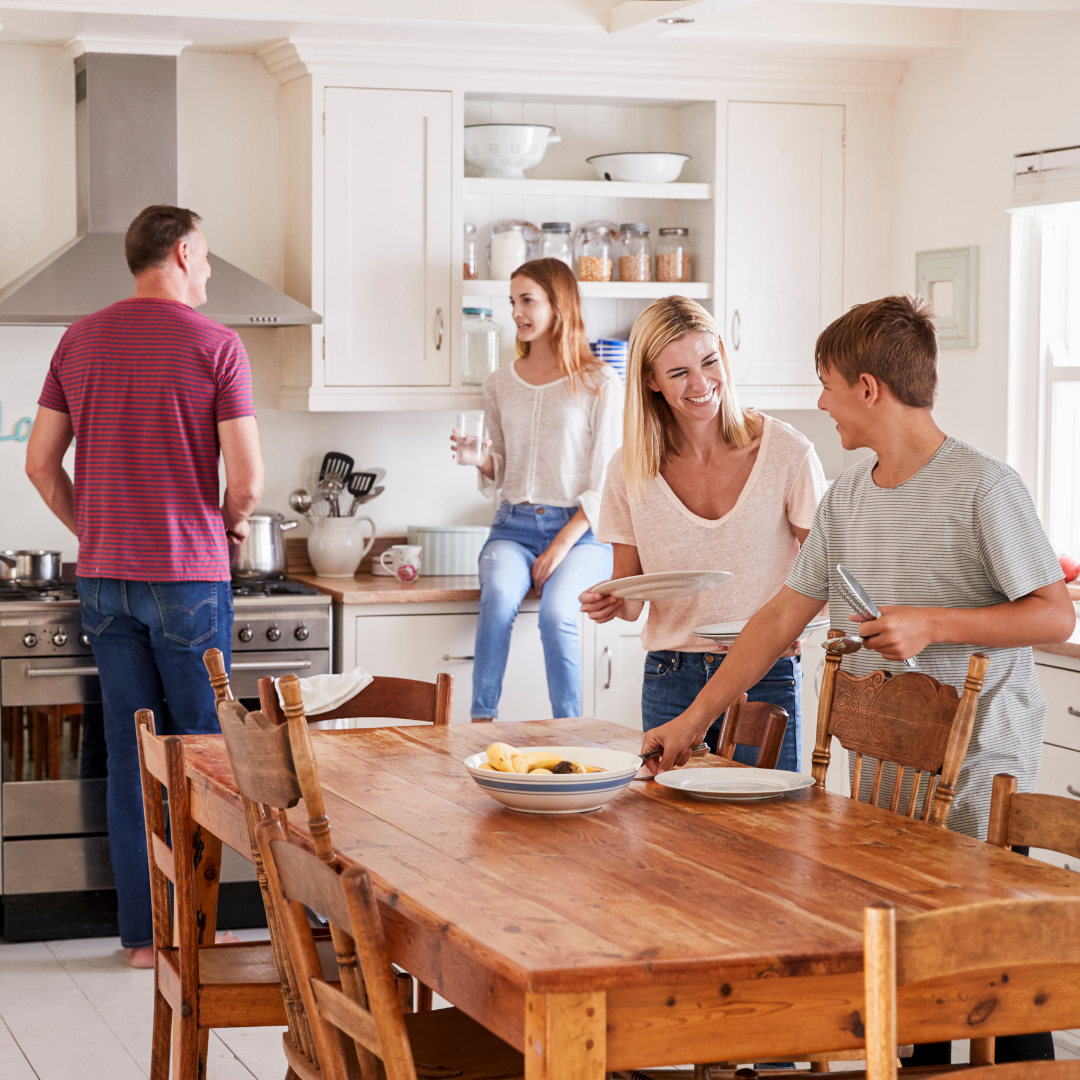 family setting the table and preparing a meal