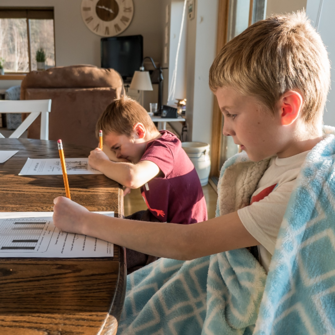 2 boys doing schoolwork at kitchen table
