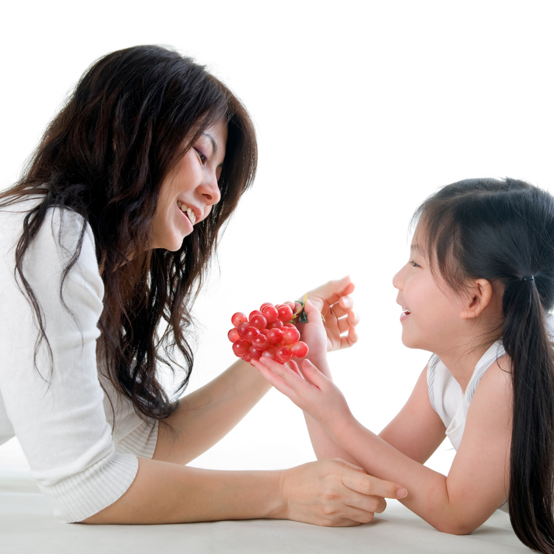 little girl and mom sharing grapes