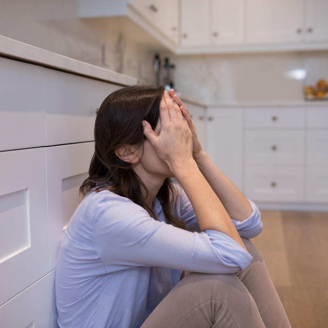 worried woman sitting on the floor