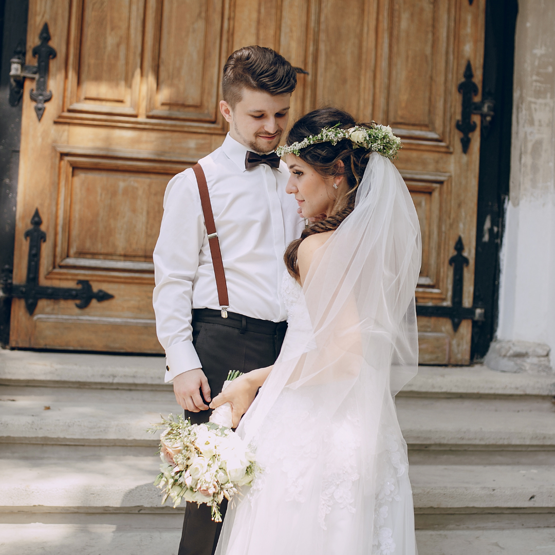 bridge and groom on steps of a church