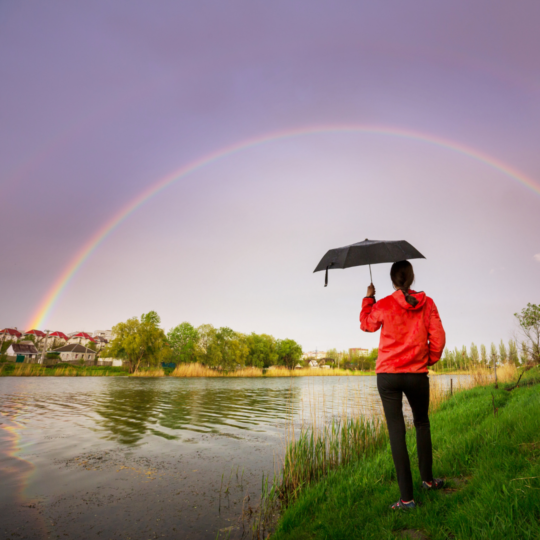 woman with umbrella looking at a double rainbow