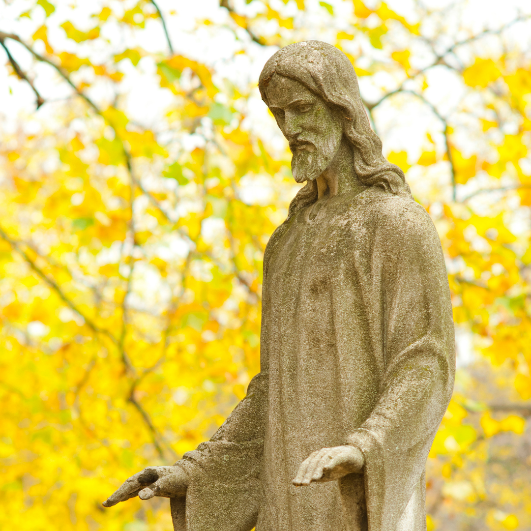 statue of Jesus with autumn leaves in the background