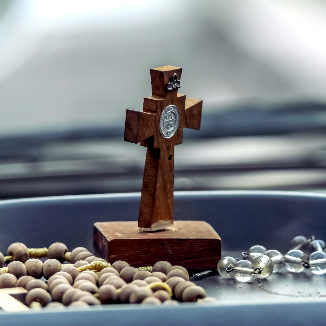 rosaries and small cross on car dashboard