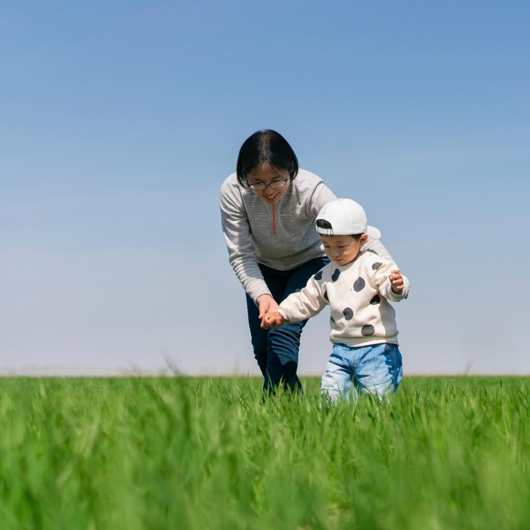 mom helping toddler walk across a field
