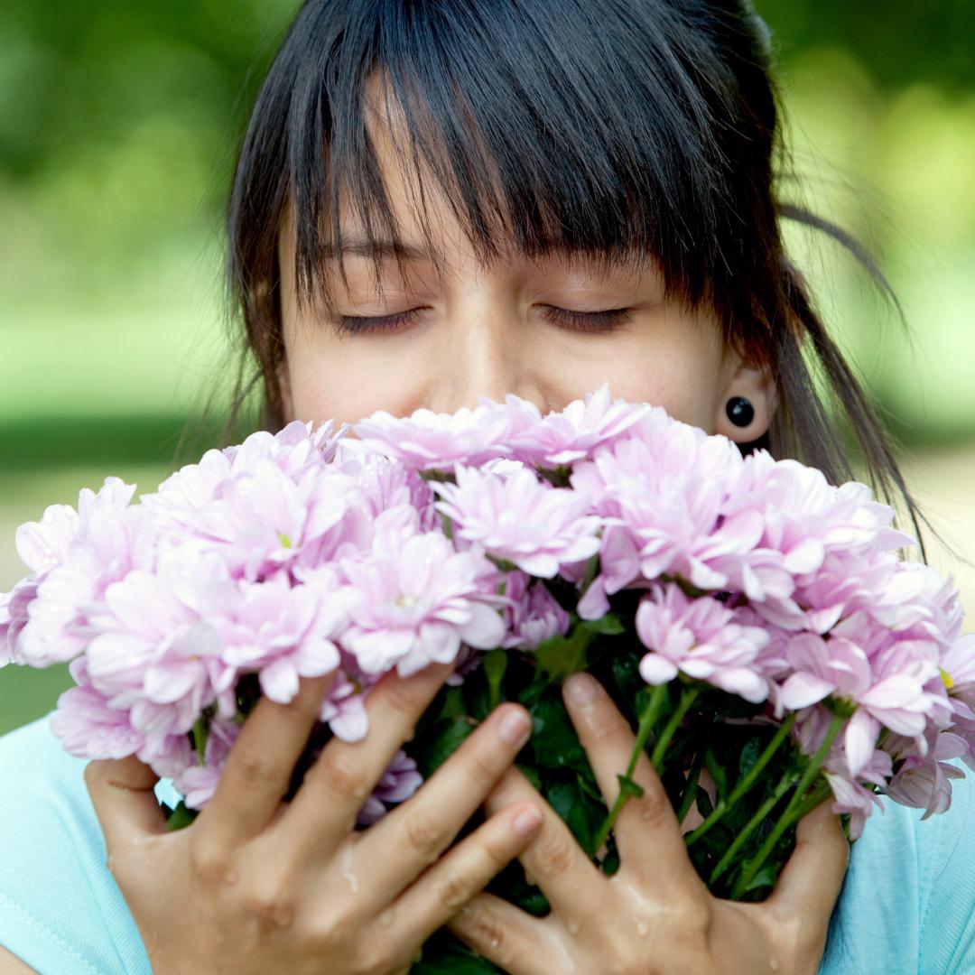 woman smelling purple flowers