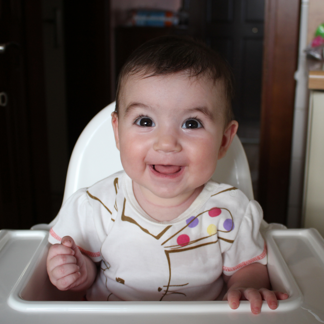smiling baby sitting in a high chair
