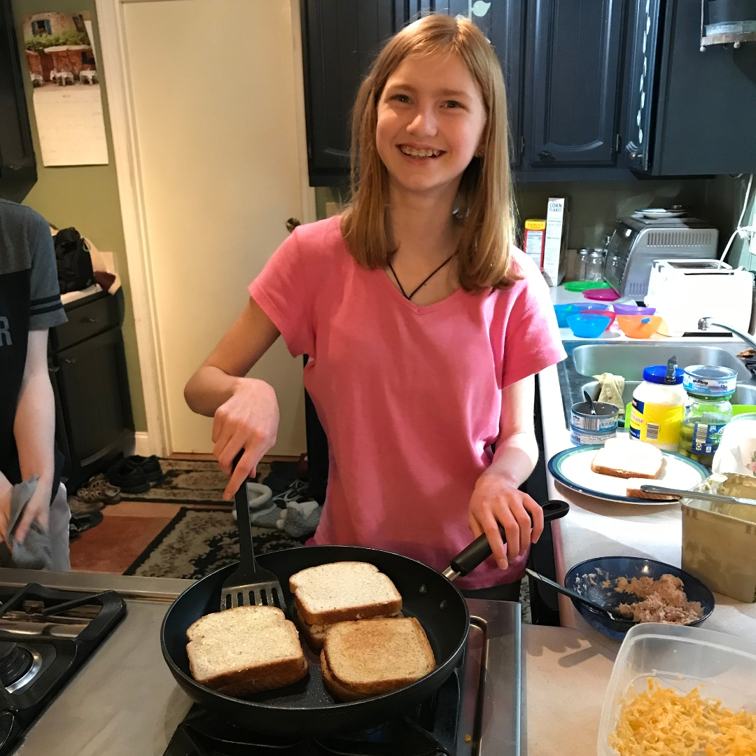 girl making grilled cheese sandwiches