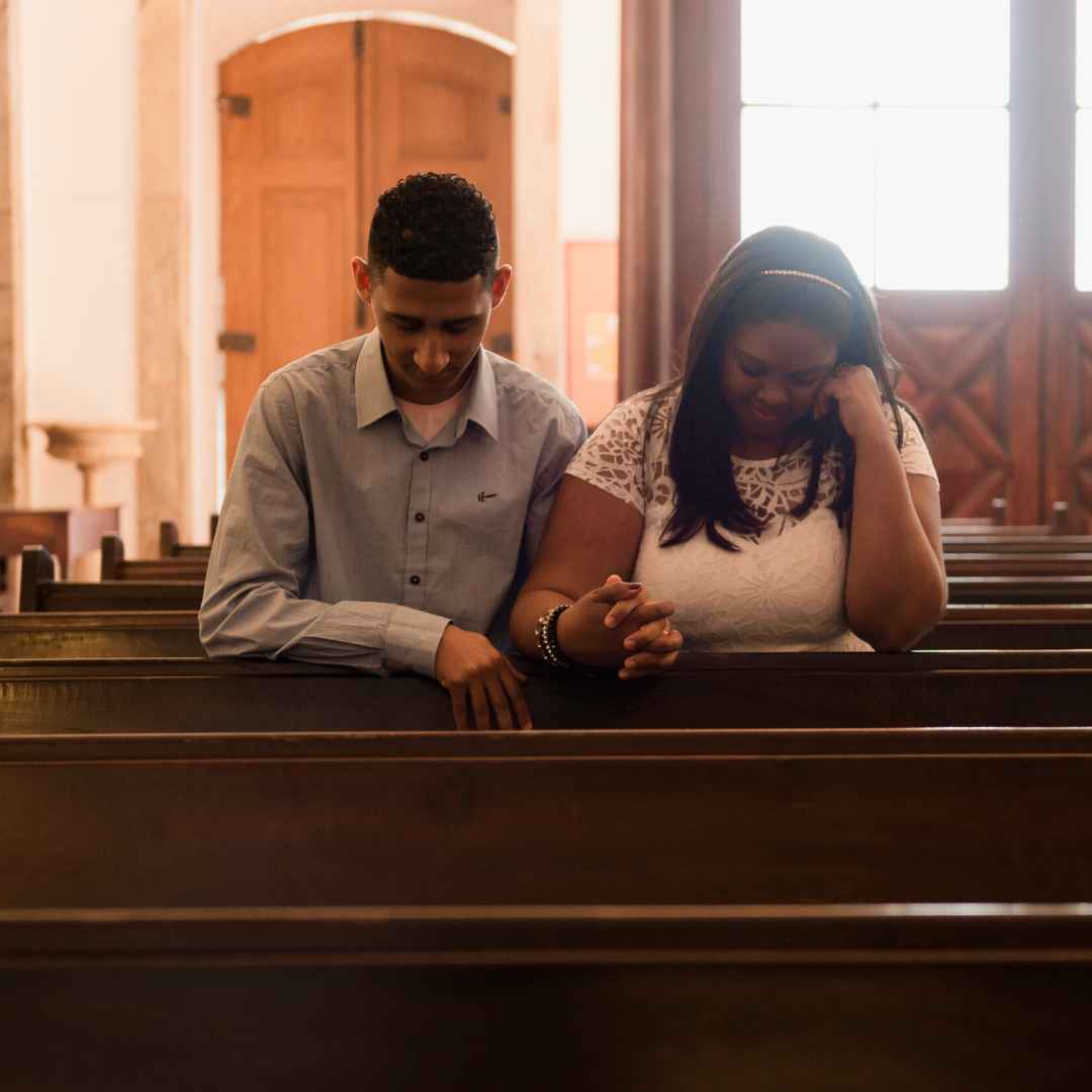 young couple praying together in a church