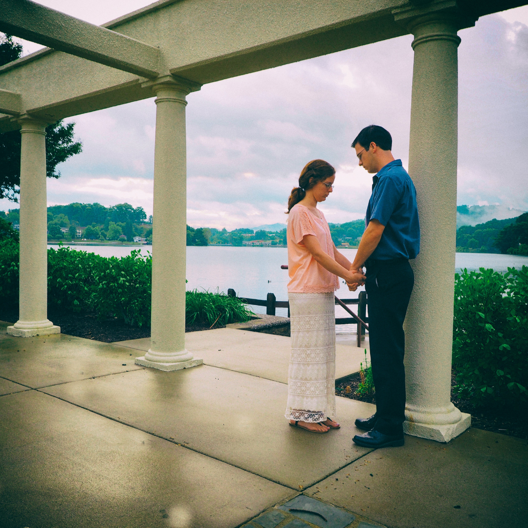 couple praying together in a gazebo