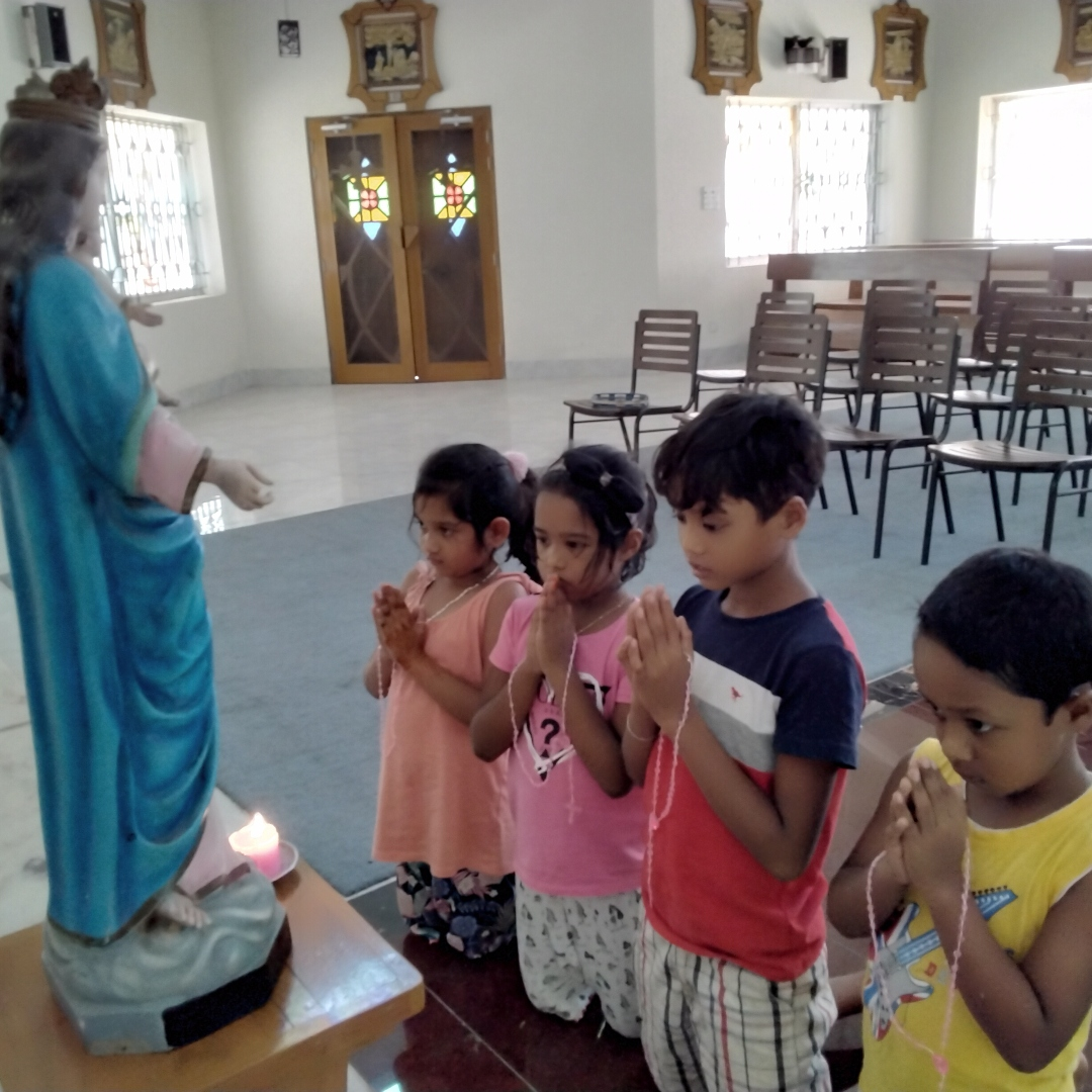 children praying in front of a statue of Mary