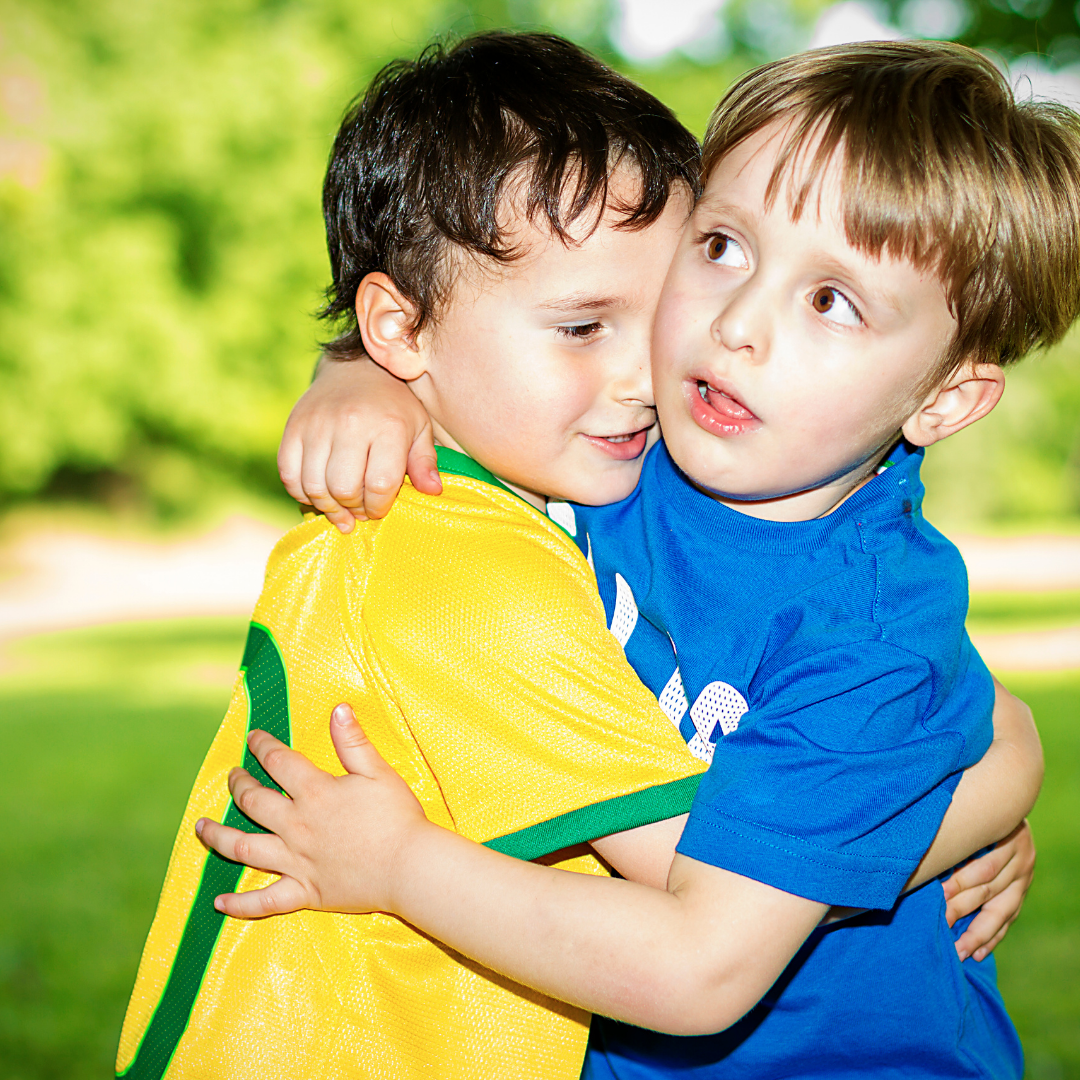 2 little boys in soccer uniforms hugging each other