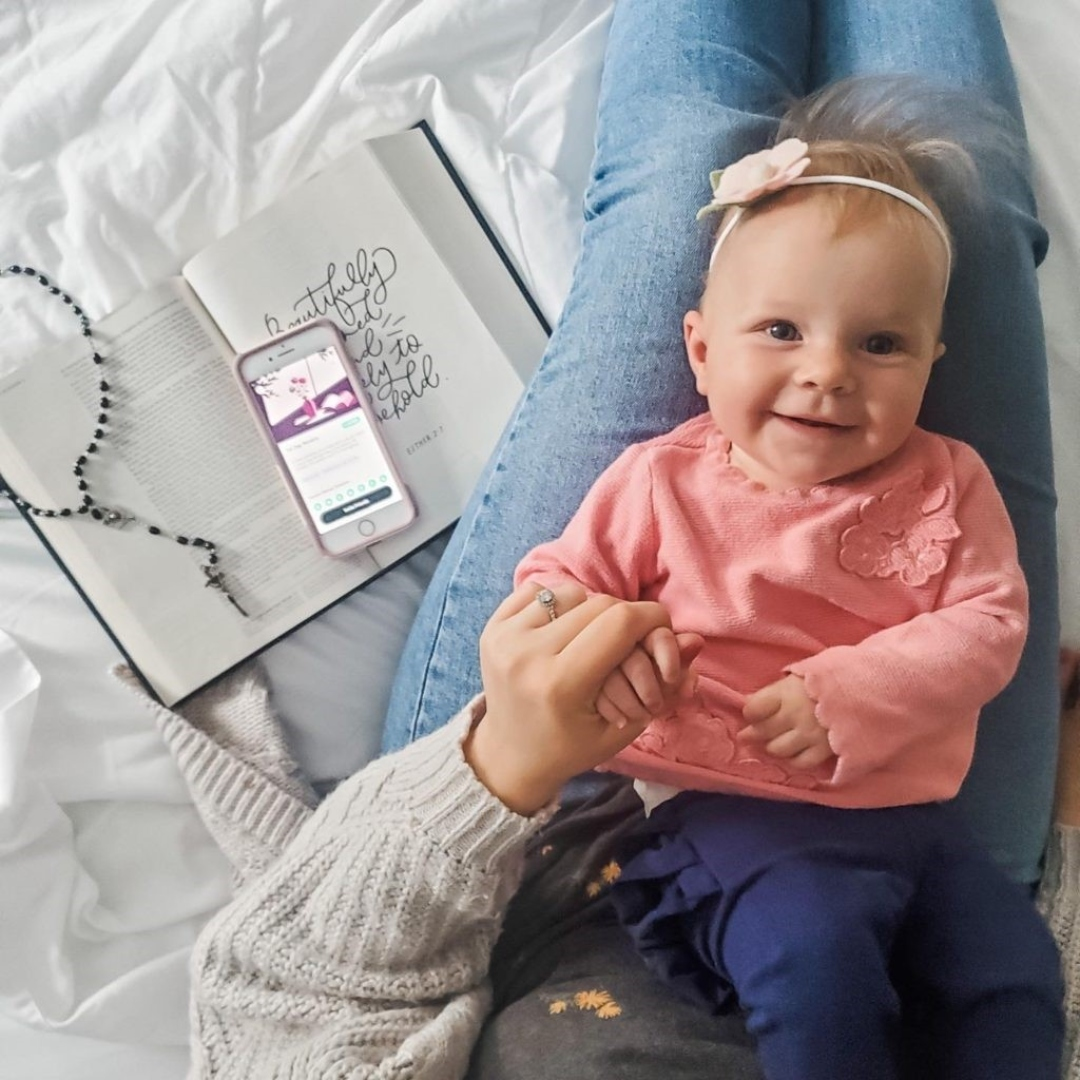 mom holding baby in her lap with Bible, Rosary, and phone open to Hallow app