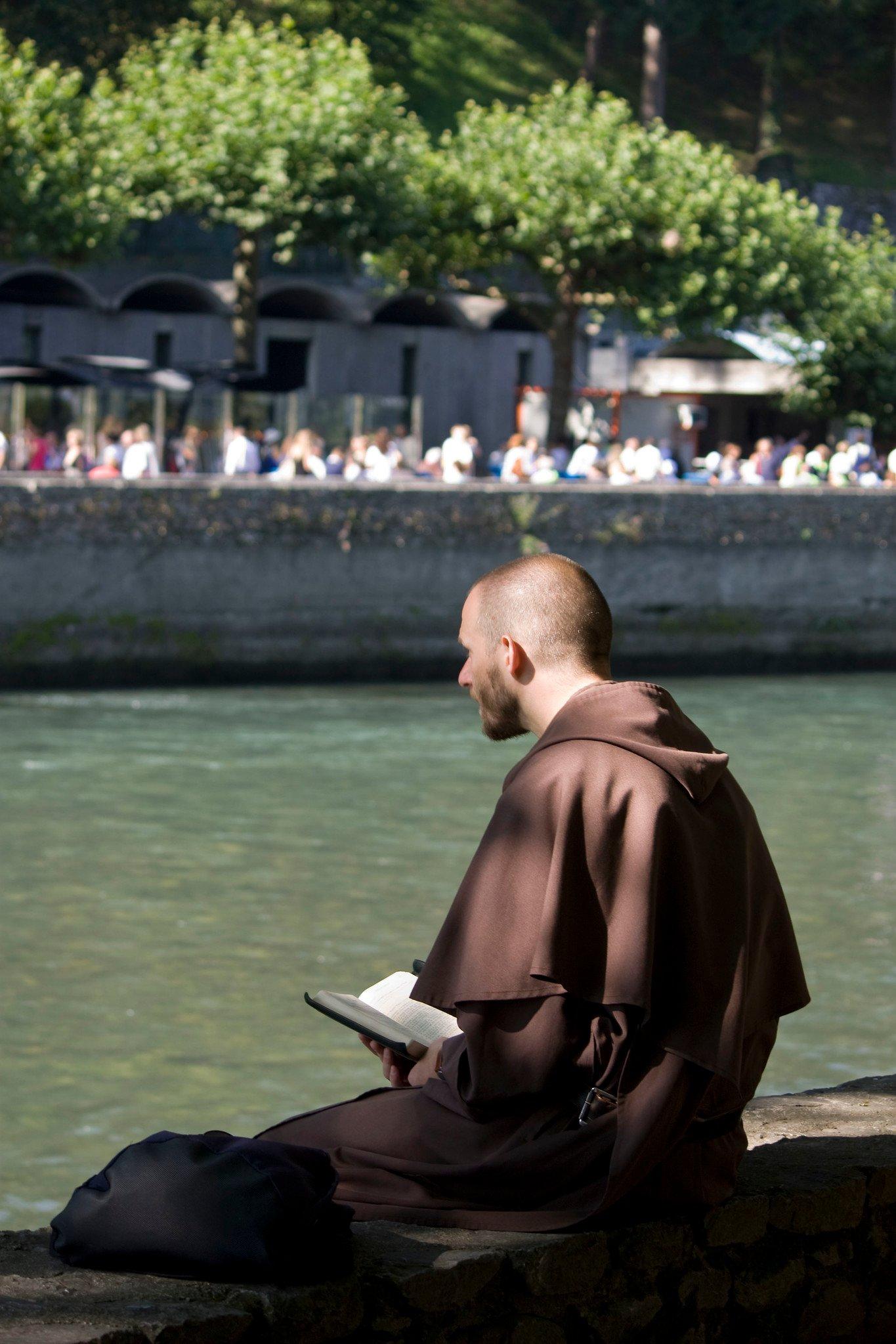 friar praying along a riverbank