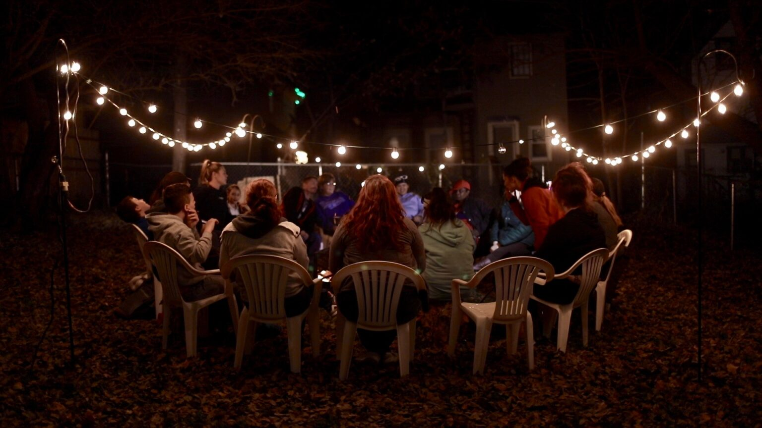 group of people sitting around a firepit in outdoor chairs with big white lights strung up around the yard