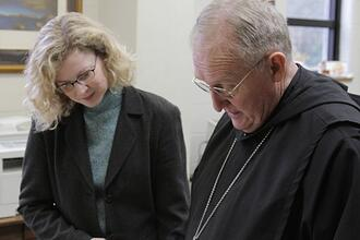 Producer Carol Ann Vaughn Cross and Abbot Cletus Meagher of Saint Bernard Abbey review archival materials