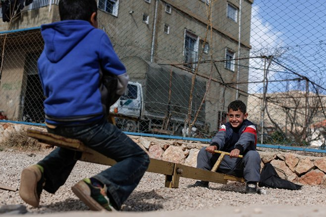 Brahim, 8, right, and Jado, 10, Syrian refugees from Aleppo province, play at the Good Shepherd Sisters center. With CRS' support, the sisters organize summer camps with various activities and provide trauma counseling. Photo by Sam Tarling for CRS