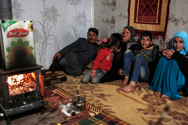 """A CRS-supplied wood-burning stove helps warm a family's tent. """"Without the heater and the wood we would have died from the cold,"""" says Sabah, the children's mother. """"It was difficult finding wood in a snowstorm,"""" she says. Photo by Sam Tarling for CRS"""
