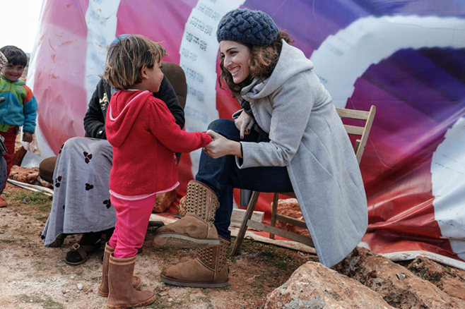 Soha Menassa, a CRS project manager in Lebanon, talks with a Syrian child from Raqqa at the Bachir informal tent settlement in Deir al Ahmar in Lebanon's Bekaa Valley. Photo by Sam Tarling for CRS