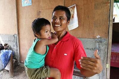 Ric De Veyra, age 30, had recently been elected Barangay chairperson but was still a month away from taking office when typhoon Haiyan / Yolanda devastated his community. When the sitting chairperson left for Manila immediately after the storm, it was up to Ric to lead the community in recovery. Here, Ric is pictured holding his 3-year-old son Joshua in front of his new CRS shelter. Jen Hardy/CRS