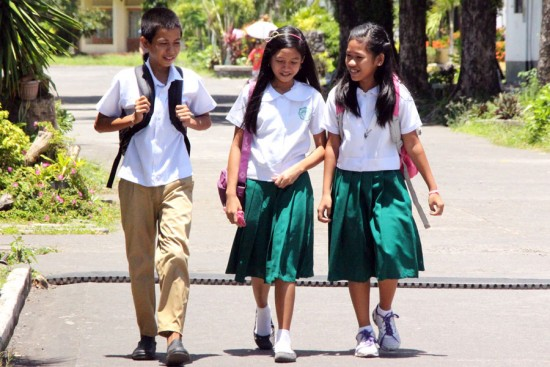 From left: Angelo, Rea and Jasmine, teens sponsored through Unbound in the Philippines, walk to school together.