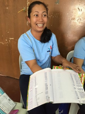 A volunteer bookkeeper from Unbound's Family Savings Program opens her accounts for us. She's received leadership and financial training to hold this important role in her small community's savings and lending program.