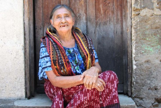 An old woman in Guatemala smiles outside her home.